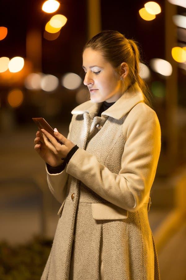 Eleganckiej kobiety pisać na maszynie wiadomość tekstowa na ulicie przy nocą zdjęcia royalty free