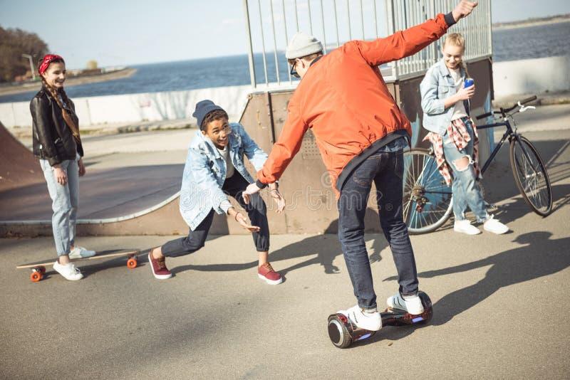 Eleganckiej modniś chłopiec jeździecki gyroboard z przyjaciółmi blisko obok fotografia royalty free
