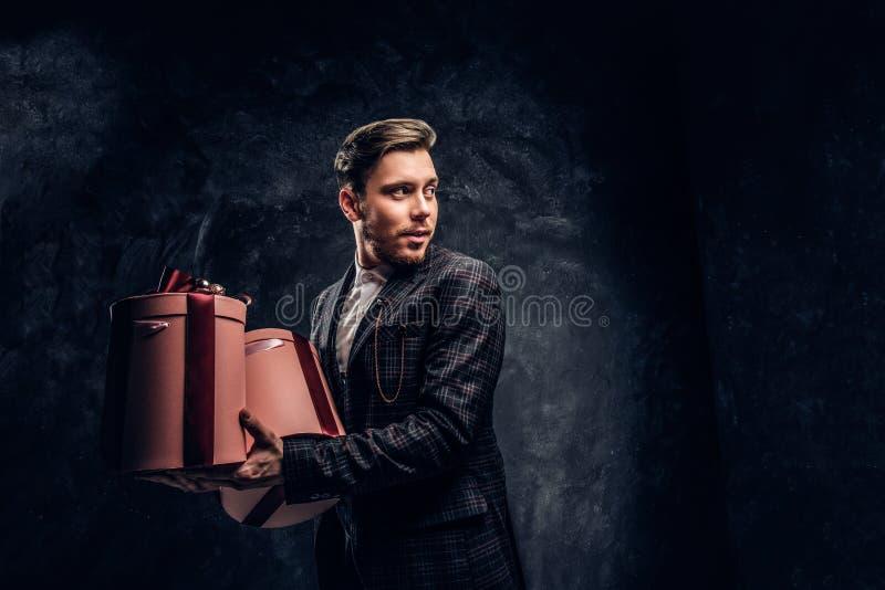 Elegancko ubierający mężczyzny mienia prezenty podczas gdy pozujący w ciemnym studiu zdjęcia royalty free