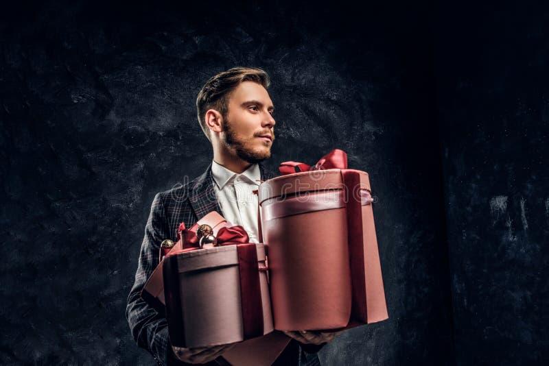 Elegancko ubierający mężczyzny mienia prezenty podczas gdy pozujący w ciemnym studiu fotografia stock