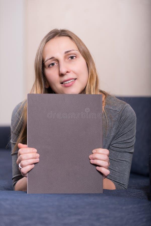 Elegancko ubierający młody brunetki kobiety vertical z magazynem zdjęcia stock
