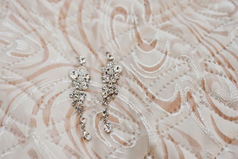 Elegancy épousant les boucles d'oreille brillantes de la jeune mariée sur la texture image stock