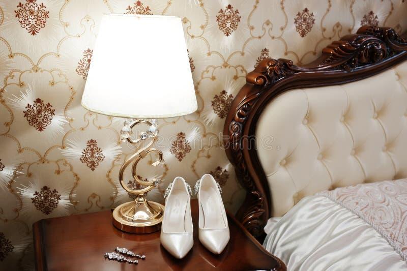 Elegancyhochzeitsschuhe der Braut mit glänzender Brosche und earrin lizenzfreies stockbild