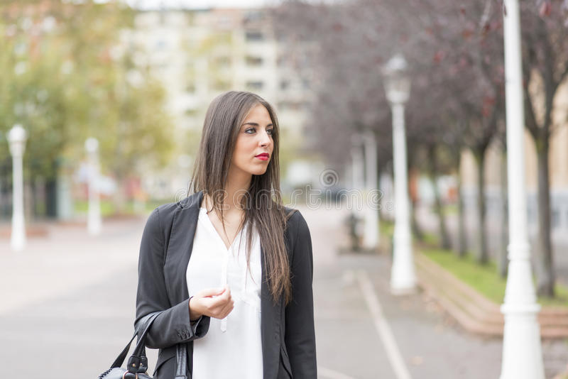 Elegand ung kvinna i gatan som bort ser royaltyfri foto