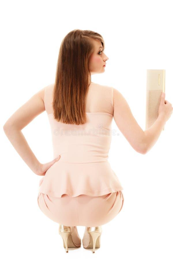 elegans Dra tillbaka av flicka i rosa färgklänning och med handväskan royaltyfri bild