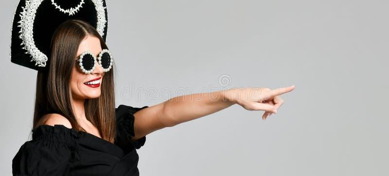Elegans och utformar Studiostående av den ursnygga unga kvinnan i den lilla svarta klänningen som poserar mot gul bakgrund royaltyfri fotografi