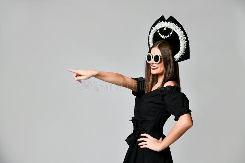 Elegans och utformar Studiostående av den ursnygga unga kvinnan i den lilla svarta klänningen som poserar mot gul bakgrund arkivfoton