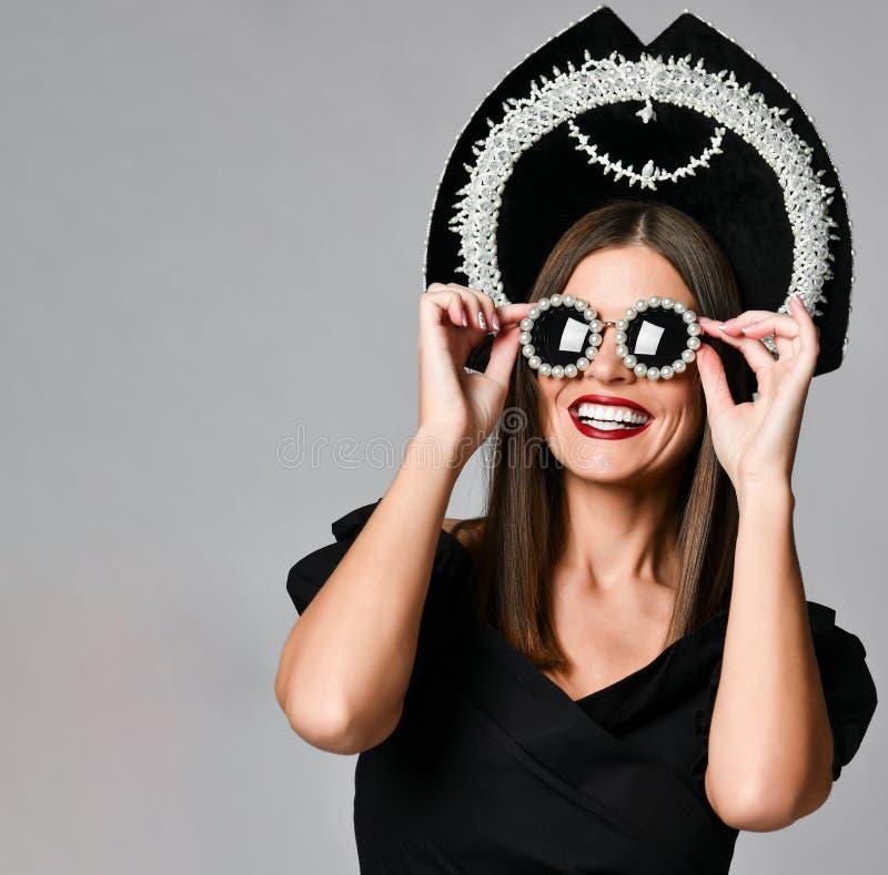 Elegans och utformar Studiostående av den ursnygga unga kvinnan i den lilla svarta klänningen som poserar mot gul bakgrund fotografering för bildbyråer