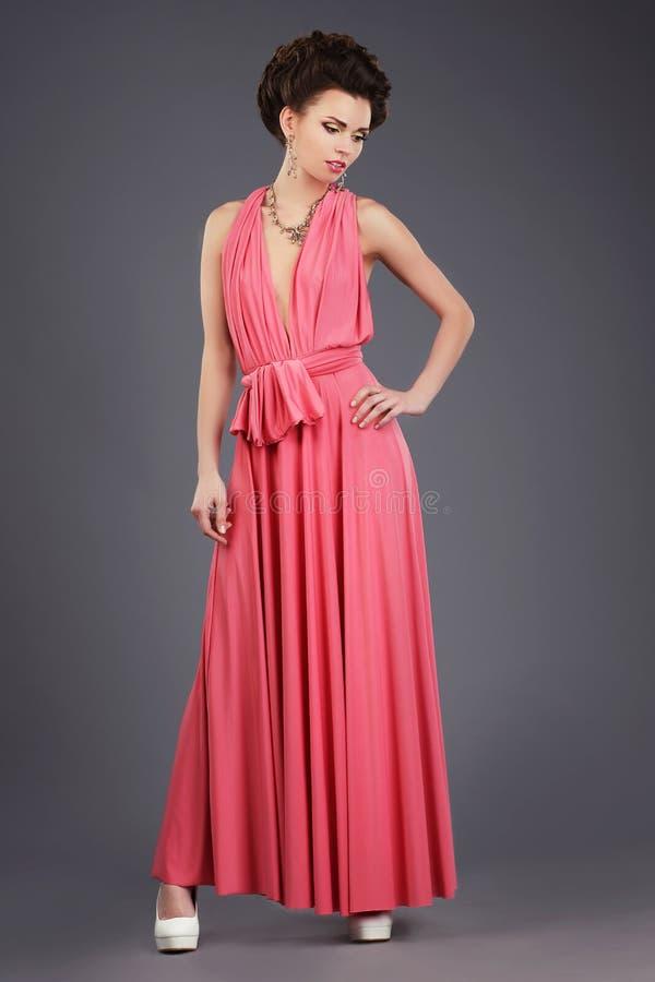 elegans Stilfull brunett i rosa festlig klänning fotografering för bildbyråer