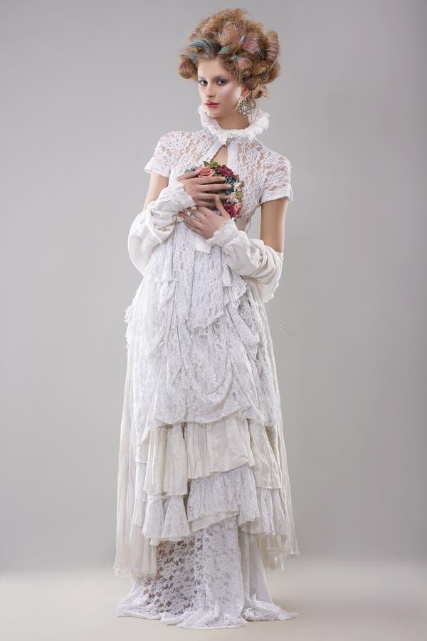 elegans Ursnygg modemodell i lång kappa och bukett av blommor royaltyfri foto