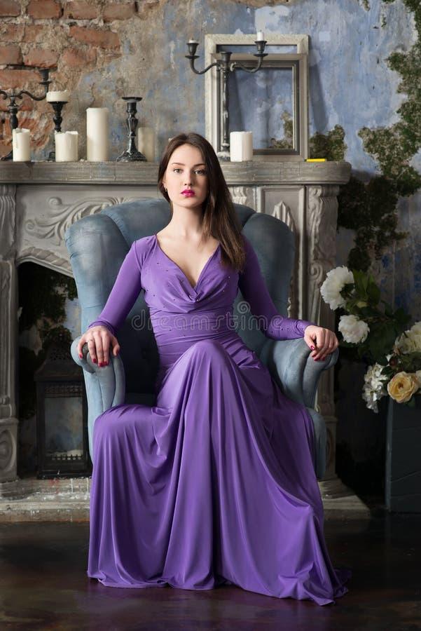 Eleganskvinna i långt violett klänningsammanträde på stol inomhus arkivfoto
