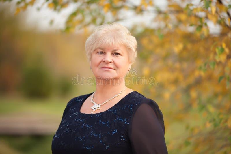 Elegant äldre kvinnastående, höstdag arkivfoto