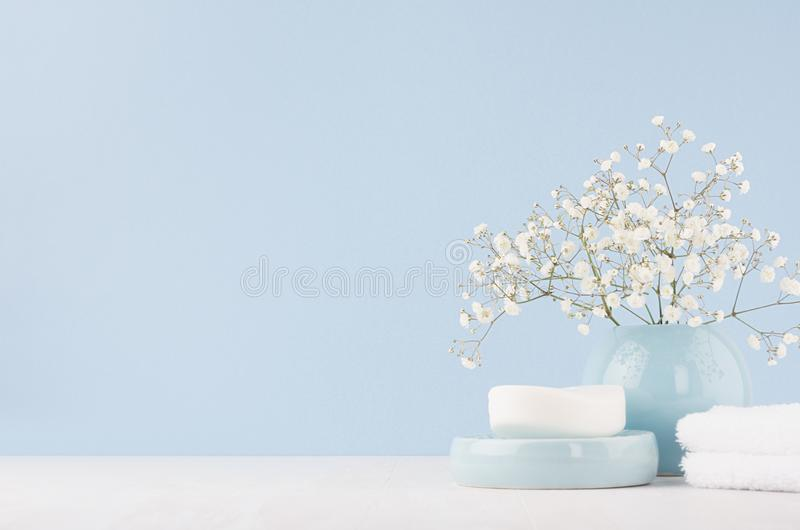 Elegant accessories for dressing table - soft pastel blue ceramic bowls, white flowers, products for skin and body care on white. royalty free stock photos