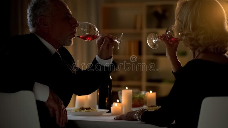 Elegant adult couple drinking wine in cafe, love togetherness, aged soul mates royalty free stock images