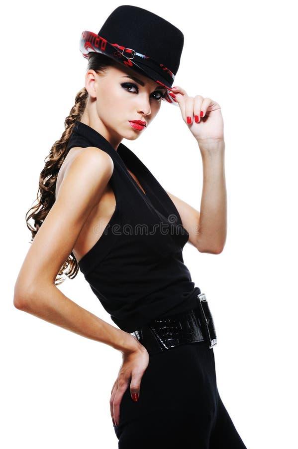Elegant adult girl in black with stylish black hat. Luxury glamour elegant adult girl in black dress with stylish black hat royalty free stock photography