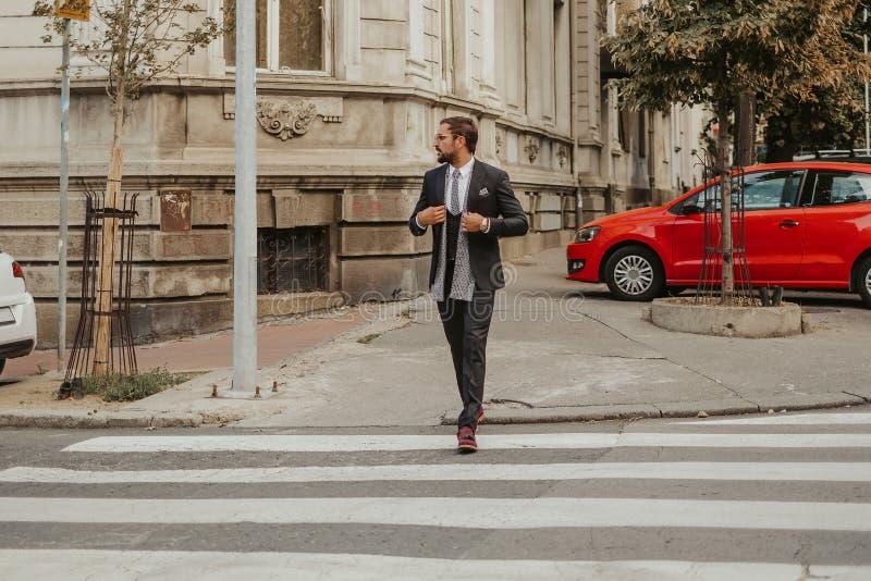 Elegant affärsman som korsar gatan fotografering för bildbyråer
