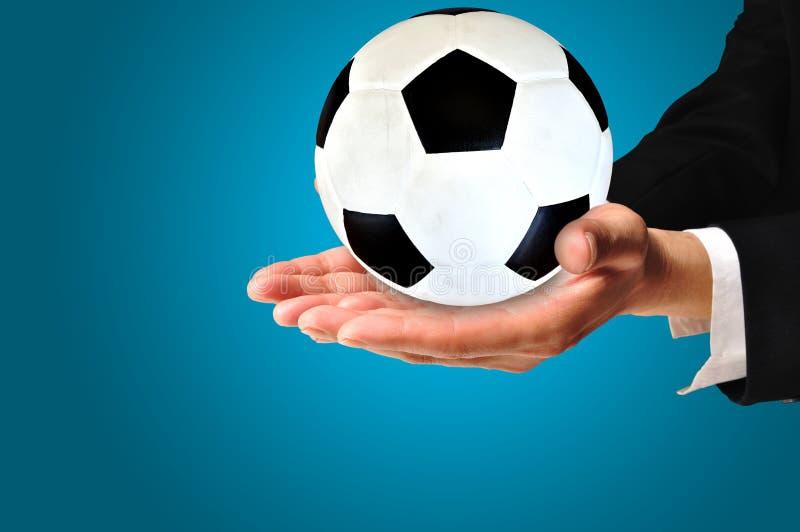 Elegant affärsman som rymmer en fotbollboll royaltyfri bild