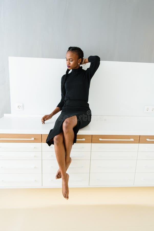 Elegant afrikan eller amerikansk kvinna för svart i mörkt klänningsammanträde på skrivbordet i ljus inre royaltyfri bild
