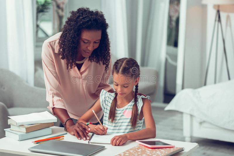 Elegant Afro-American mom assisting her daughter with doing a homework. royalty free stock images