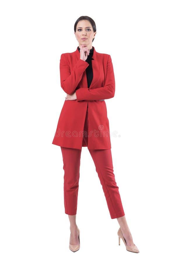 Elegant allvarlig attraktiv affärskvinna i röd dräkt med handen på hakan som ser kameran royaltyfri fotografi