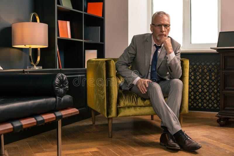 Elegant allvarlig hög man som sitter i hans kontor arkivbild