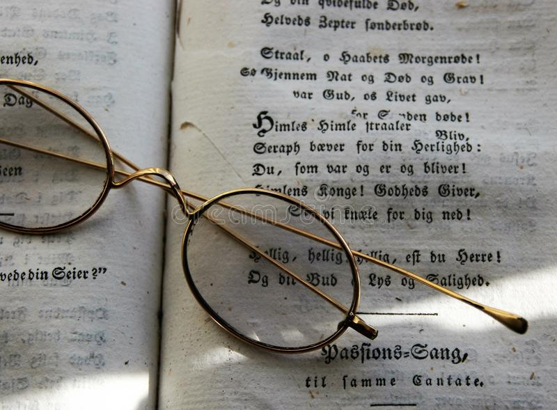 Elegant and antique glasses on a book stock photography