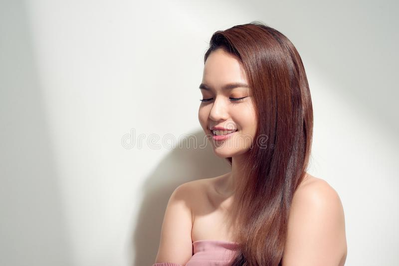 Elegant asian girl with tanned skin posing with pensive face expression on bright background royalty free stock images