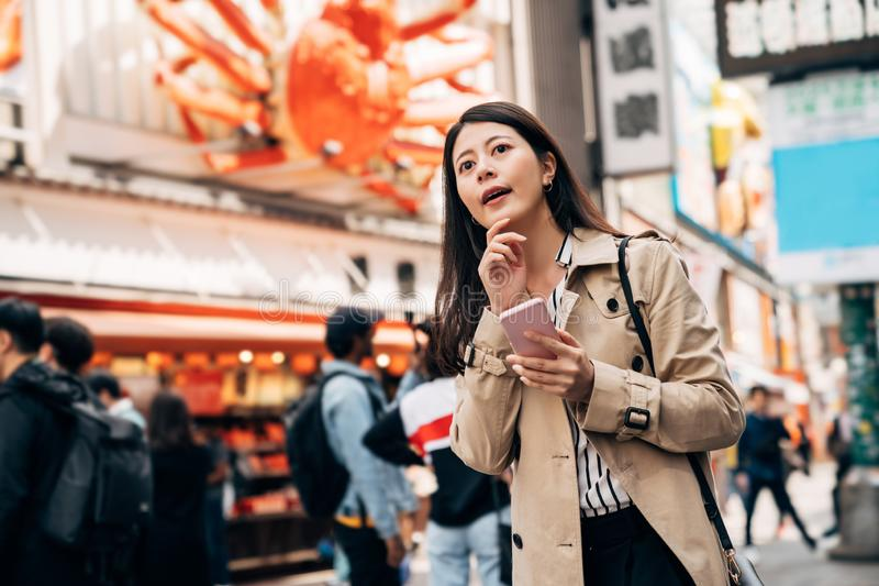 Elegant Asian girl using phone finding hotel stock photography