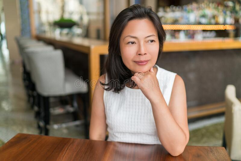 Elegant Asian middle-aged businesswoman pensive portrait. Beautiful mature Chinese business woman relaxing in restaurant royalty free stock image