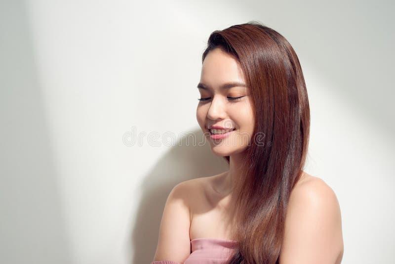 Elegant asiatisk flicka med brunbr?nd hud som poserar med eftert?nksamt framsidauttryck p? ljus bakgrund royaltyfria bilder