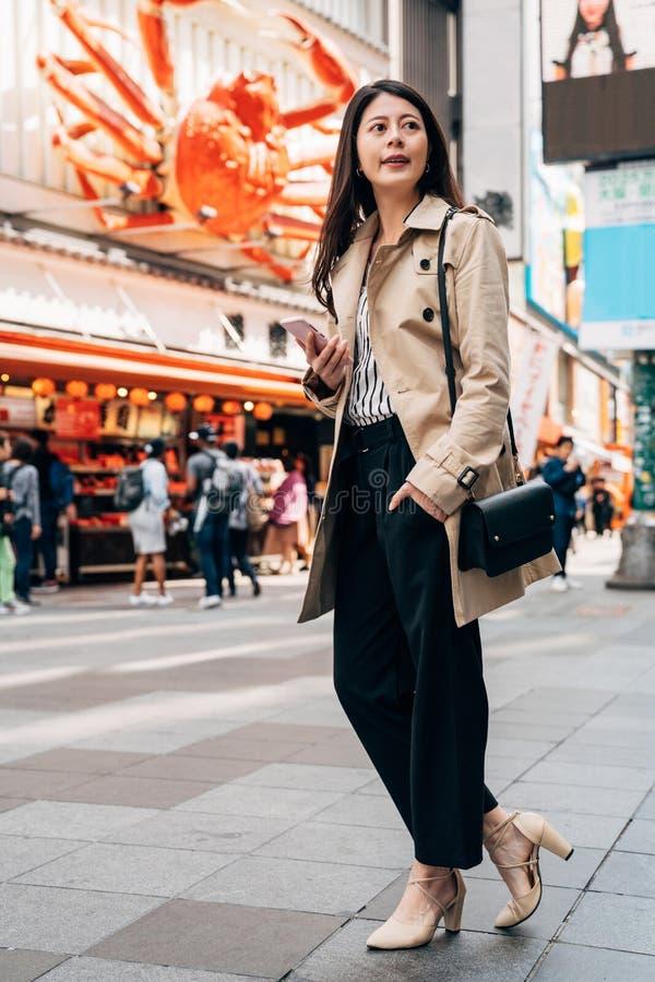 Elegant Aziatisch meisje die telefoon met behulp van die richting controleren stock afbeeldingen