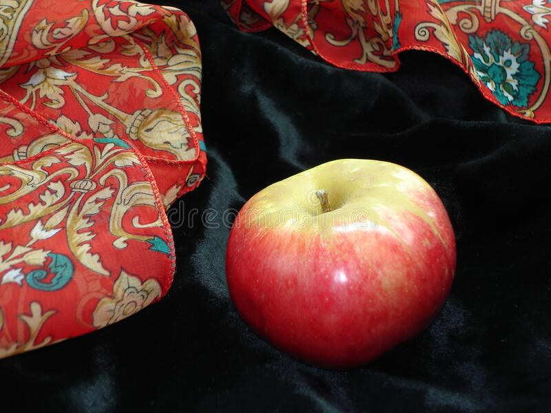 Red-yellow fresh apple on a background of black glossy velvet and fabric with a red pattern stock photo