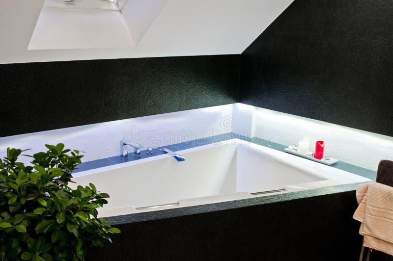 Elegant badrumdetalj med hörnbadkaret och blå ledd belysning arkivfoto