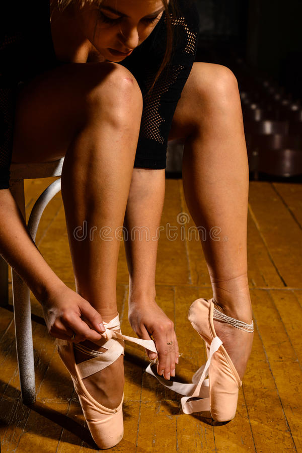 Elegant ballet dancer tying her pointe shoes royalty free stock photo