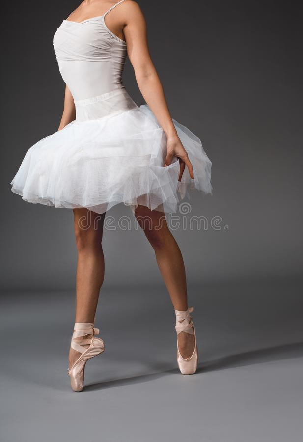 Elegant ballet performer balancing on tiptoe. Airiness concept. Female body in tutu and satin slippers walking at the tips of her toes royalty free stock image