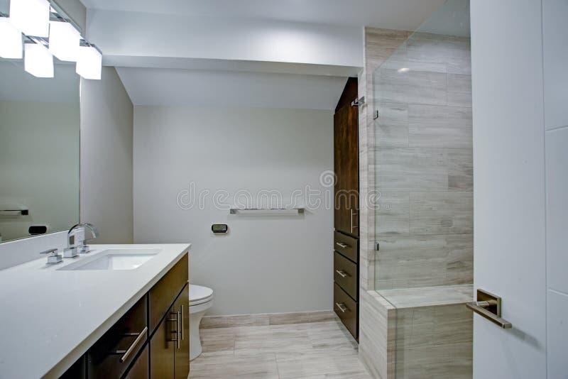 Elegant bathroom with marble bathroom floor. Elegant bathroom with espresso double vanity, glass shower and grey marble floor stock photo