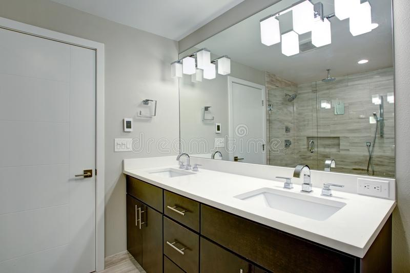 Elegant bathroom with espresso double vanity. With pure white countertops, undermount sinks, large mirror and glass shower royalty free stock photos