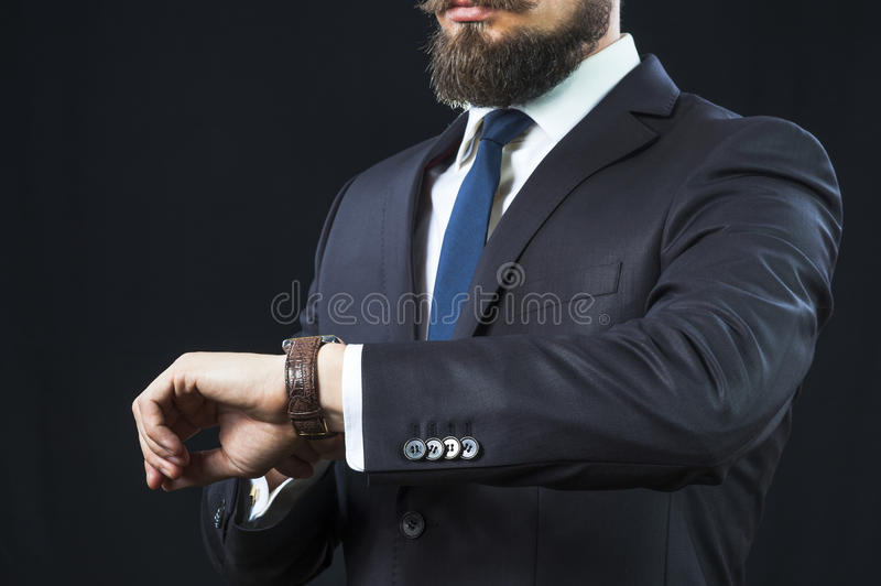 Elegant bearded man in suit looking at his watch. stock photo