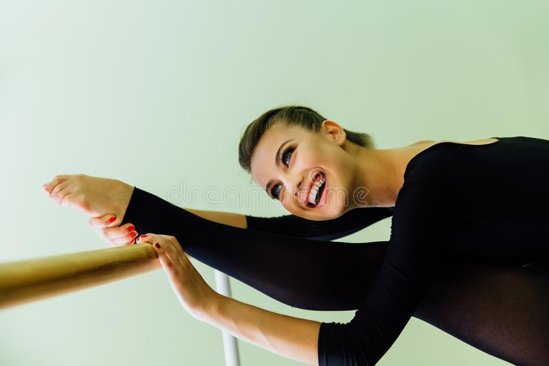 Elegant beautiful ballerina with a perfect body doing stretching exercise. royalty free stock image