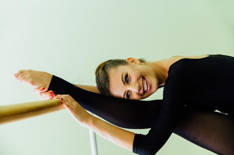 Elegant beautiful ballerina with a perfect body doing stretching exercise. royalty free stock photo