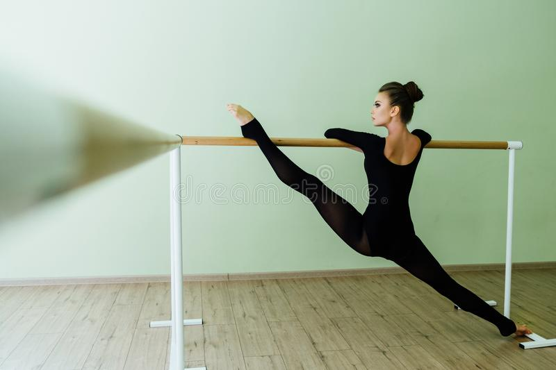 Elegant beautiful ballerina with a perfect body doing stretching exercise. stock photography