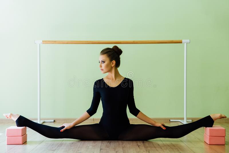 Elegant beautiful ballet dancer girl with perfect body sits on the floor. royalty free stock photo