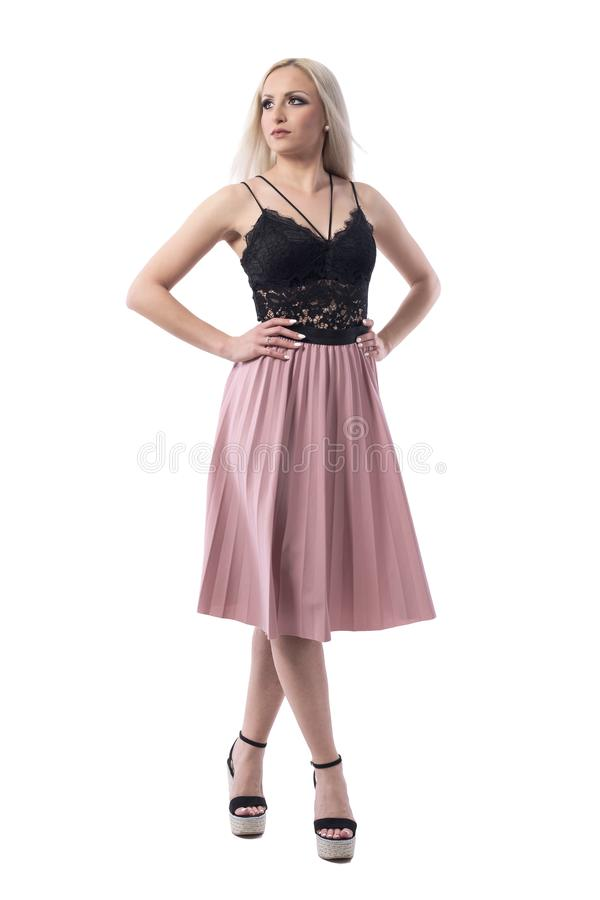 Elegant beautiful blonde fashion model in summer stylish clothes looking up with hands on hips stock photos