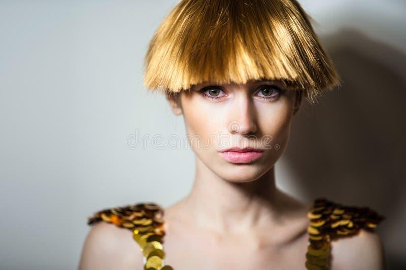 Elegant beautiful blonde woman posing in studio, wearing fashionable dress royalty free stock photos