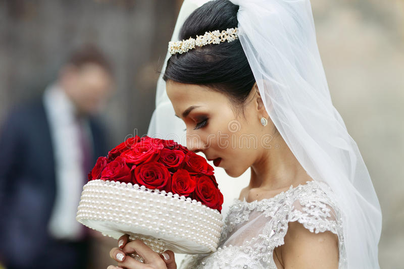 Elegant beautiful brunette bride walking down old european street with handsome groom in the background closeup stock photos