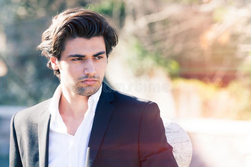 Elegant beautiful business pensive man. A handsome young man outdoors. Stylish hair and intense beauty. Jacket with white shirt. Intense sun stock image