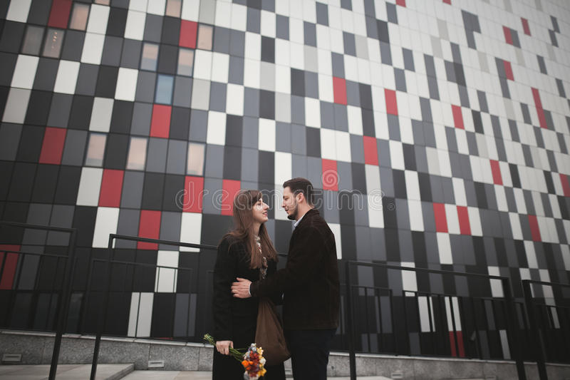 Elegant beautiful couple posing near modern glass building stock photography