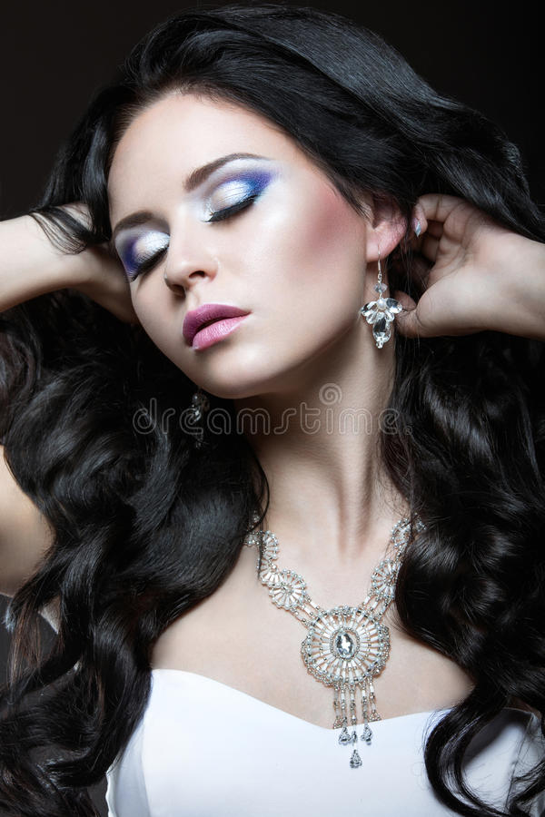 Elegant beautiful girl with silver makeup and black curls. Winter image. Beauty face. stock photos