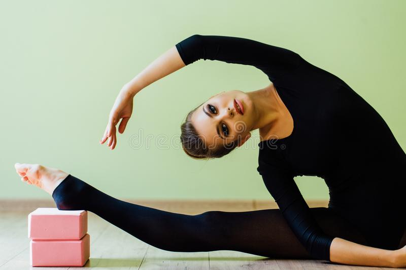 Elegant beautiful modern ballet dancer girl with perfect body sits on the floor on on twine. royalty free stock image