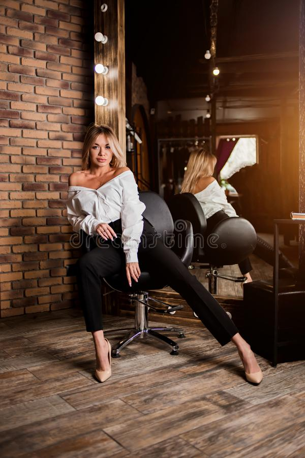 Elegant beautiful sexy young woman in white shirt, black trousers sitting in chair next to large mirror. Loft style interior. Fashion, style, beauty, glamour royalty free stock photography
